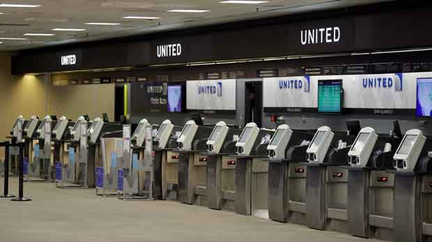 empty United Airlines ticket machines are shown at the Tampa International Airport in Tampa, Fla