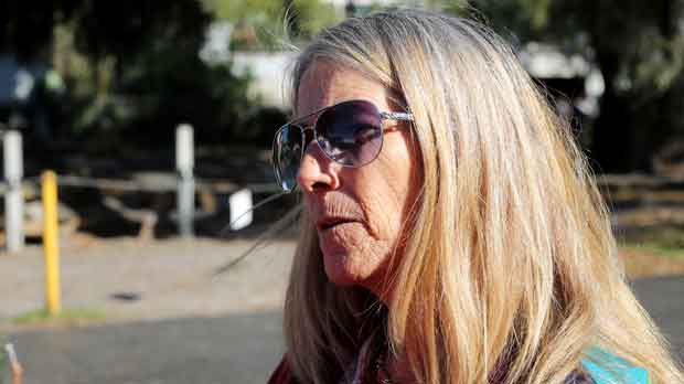 Diane Coleman speaks with homeless individuals outside of Interfaith Emergency Services