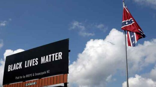 A Black Lives Matter billboard is seen next to a Confederate flag