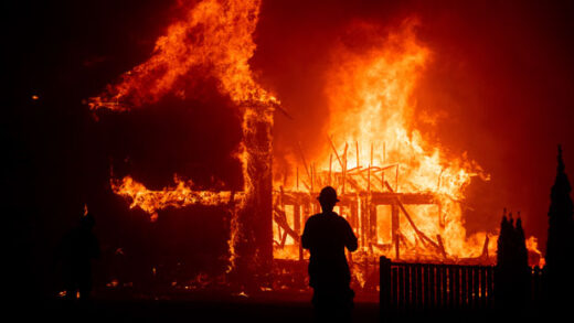 a home burns as the Camp Fire rages