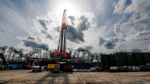 the sun shines through clouds above a shale gas drilling site