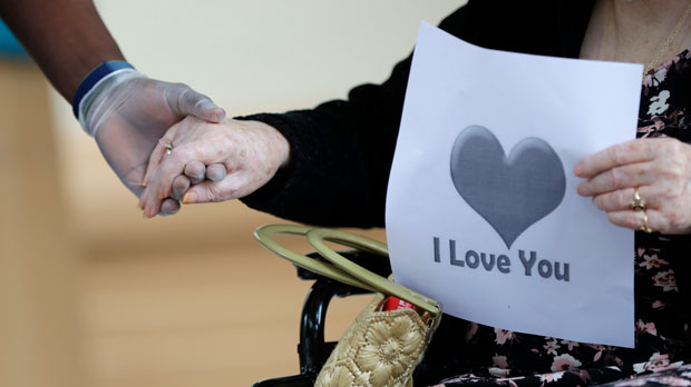 a senior citizen holds the hand of a care coordinator