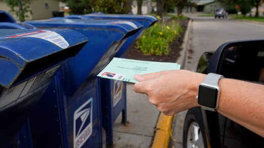 person drops applications for mail-in-ballots