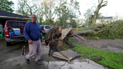 a MAN walks past a downed tree in his yard