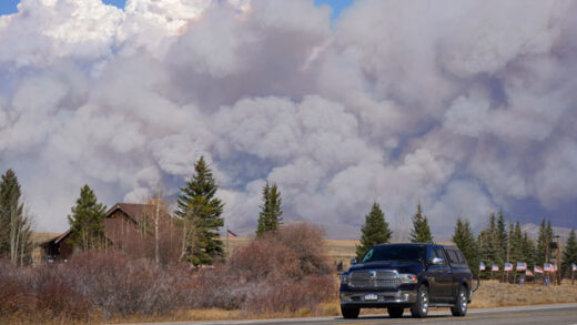 Smoke rises from mountain ridges