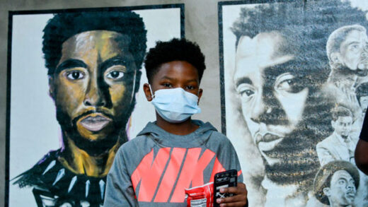 A boy stands in front of two paintings of Chadwick Boseman