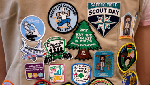 patches cover the back of a Girl Scout's vest