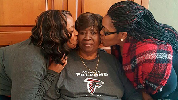 Bessie Burden, center, gets kisses from her daughters Theresa Burrough, left and Lashieka Mitchell