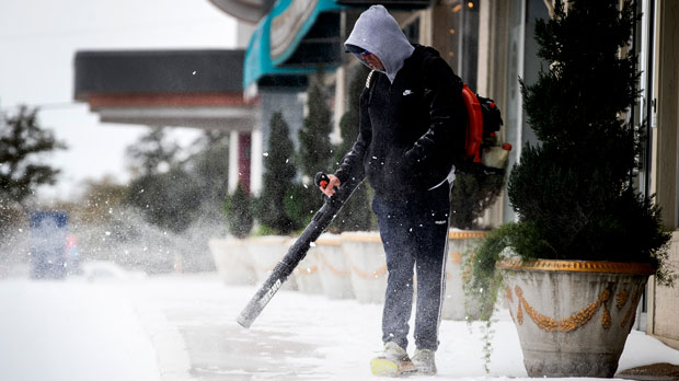 a man uses a blower to clear the sidewalks
