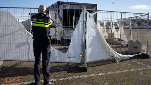 a police officer takes pictures of a burned-out coronavirus testing facility