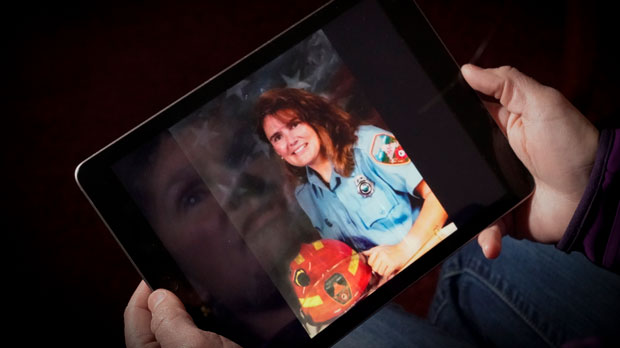 A woman looks at her fire fighter portrait