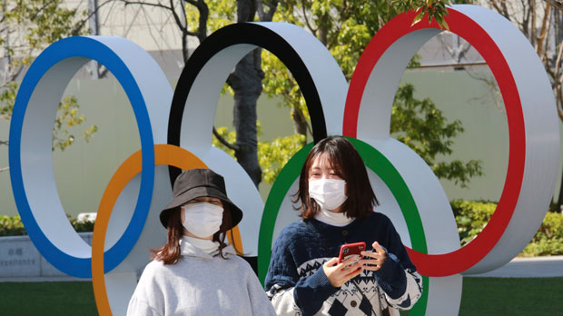 people walk past the Olympic rings in Tokyo