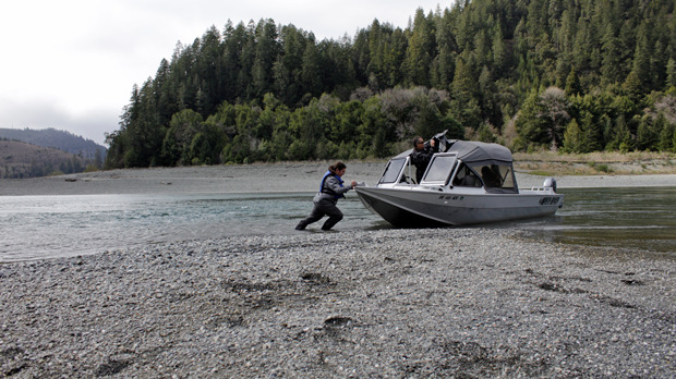 Person pushes a jet boat into the low water