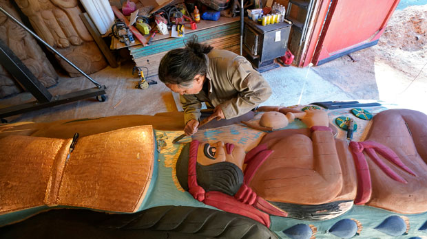 Lummi Nation lead carver Jewell James works on the final details of a nearly 25-foot totem pole to be gifted to the Biden administration