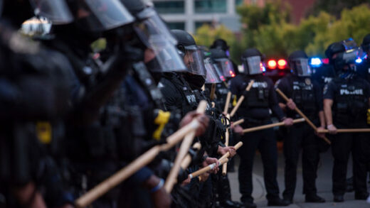 a line of police officers block protesters