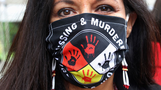 Jeannie Hovland poses with a Missing and Murdered Indigenous Women mask