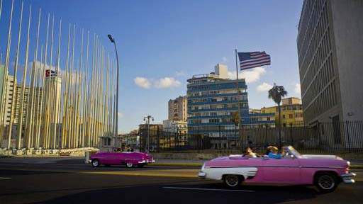 Tourists ride in classic American convertible cars past the United States embassy, right, in Havana, Cuba, Thursday, Jan. 12, 2017. President Barack Obama announced Thursday he is ending a longstanding immigration policy that allows any Cuban who makes it to U.S. soil to stay and become a legal resident. (AP Photo/Ramon Espinosa)