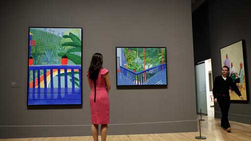 """A Tate representative poses for photographs next to David Hockney's Los Angeles garden paintings """"Two Pots on the Terrace"""", left, and """"Garden #3"""" during a photocall to promote the largest-ever retrospective of his work at Tate Britain gallery in London, Monday, Feb. 6, 2017. The exhibition, which opens to the public from February 9 and runs until May 29, celebrates the 79-year-old's achievement in painting, drawing, photography and video. (AP Photo/Matt Dunham)"""