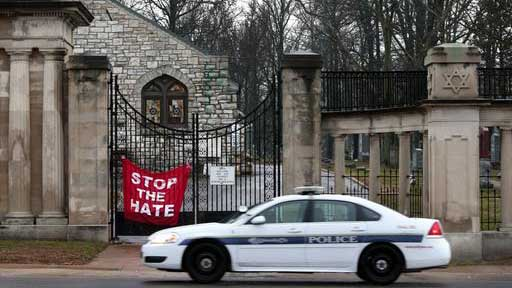 A University City police car patrols in front of Chesed Shel Emeth Cemetery in University City, Mo., on Tuesday, Feb. 21, 2017. Authorities in Missouri are investigating after dozens of headstones were tipped over at the Jewish cemetery near St. Louis. (Robert Cohen /St. Louis Post-Dispatch via AP)