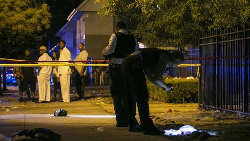 FILE - In this Aug. 7, 2016 file photo, Chicago police investigate a scene in Chicago where gunfire at a birthday party left a man dead and a woman injured. August was the deadliest month for Chicago homicides in two decades, and an analysis of the toll shows more clearly than ever that the blame lies with surging violence in a handful of the city's most impoverished neighborhoods riven by loosely organized street gangs. (Ashlee Rezin  /Chicago Sun-Times via AP, File)