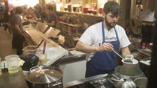 Jarrett O'Hara prepares a meal for a costumer at the Rooster Soup Co. in Philadelphia, Monday, Jan. 23, 2017. The restaurateurs have found a valuable use for their discarded chicken backs: making soup for charity. All proceeds after expenses will benefit Broad Street Ministry, a local nonprofit serving the hungry and homeless. (AP Photo/Matt Rourke)