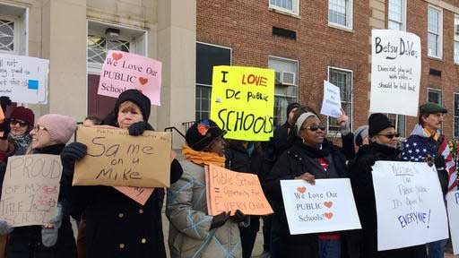 Protesters gather outside Jefferson Middle School in Washington, Friday, Feb. 10, 2017, where Education Secretary Betsy DeVos paid her first visit as education secretary in a bid to mend fences with educators after a bruising confirmation battle. (AP Photo/Maria Danilova)