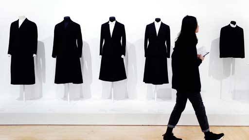"In this March 16, 2017 photo, a visitor to the Brooklyn Museum in New York walks past a display of black wool suits worn by American artist Georgia O'Keeffe. Exhibit coordinator Lisa Small said O'Keeffe's ""distinctive"" clothing style symbolized her lifelong commitment to minimalism. O'Keeffe died in 1986 at age 98. (AP Photo/Mark Lennihan)"