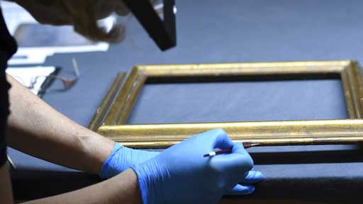An employee works on a frame during a press talk on the preparations of an exhibition of exemplary works from the Gurlitt found, an art collection of Cornelius Gurlitt discovered in 2012, in November in Bonn, Germany,  Tuesday June, 27, 2017. (Henning Kaiser/dpa via AP)