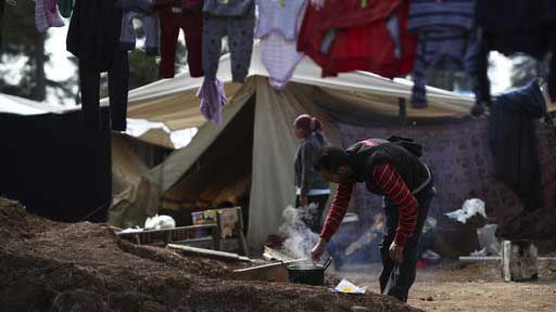 A Syrian man cooks outside his tent at Ritsona refugee camp north of Athens, on Wednesday, Oct. 19, 2016. About 600 people, mostly families with small children, live in tents in the camp, which officials say will soon be replaced by prefabricated homes. (AP Photo/Petros Giannakouris)
