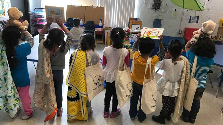 """Children receive """"Night Night"""" tote bags. Photo Courtesy of: Project Night Night."""