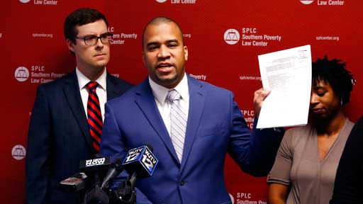 Jody Owens, director of the Mississippi office of the Southern Poverty Law Center, holds up a copy of a lawsuit filed on behalf of four African-American mothers with children in public elementary schools during a news conference in Jackson, Miss., Tuesday, May 23, 2017.   Mississippi is denying good schools to African American students and violating the federal law that enabled the state to rejoin the union after the Civil War, the Southern Poverty Law Center alleged Tuesday in a lawsuit trying to strengthen constitutional protections for education.   (AP Photo/Rogelio V. Solis)