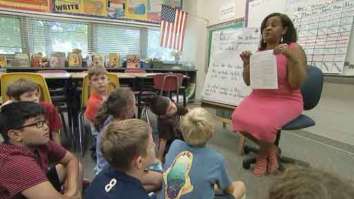 In this Tuesday, Sept. 13, 2016 still image from video, Kimberly Coleman-Mitchell, right, teaches her fourth grade class at Oakridge Elementary School in Arlington, Va. Elementary schools in Arlington, South Burlington, Vt., and Holyoke, Mass., are among those that went homework-free at the start of the school year. (AP Photo/Bill Gorman)