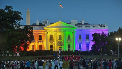 """FILE - In this Friday, June 26, 2015 file photo, people gather in Lafayette Park to see the White House illuminated with rainbow colors in commemoration of the Supreme Court's ruling to legalize same-sex marriage in Washington. It was a new look for the White House: illuminated in rainbow colors to celebrate the Supreme Court decision allowing same-sex marriage nationwide. President Barack Obama, who was inside, felt the glow on that June night in 2015. To see people gathered in the evening outside on a beautiful summer night, and to feel whole and to feel accepted, and to feel that they had a right to love _ that was pretty cool,"""" he said a few days later. (AP Photo/Pablo Martinez Monsivais, File)"""
