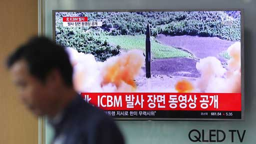 """A man walks by a TV screen showing a local news program reporting about North Korea's missile firing at Seoul Train Station in Seoul, South Korea, Wednesday, July 5, 2017. North Korea's leader Kim Jong Un vowed his nation would """"demonstrate its mettle to the U.S."""" and never put its weapons programs up for negotiations a day after test-launching its first intercontinental ballistic missile. The hard line suggests more tests are being prepared as the country tries to perfect a nuclear missile capable of striking anywhere in the United States. The letters read """"North Korea, release an ICBM launching video."""" (AP Photo/Lee Jin-man)"""