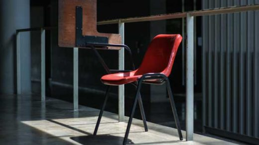 gray and red chair near the glass wall